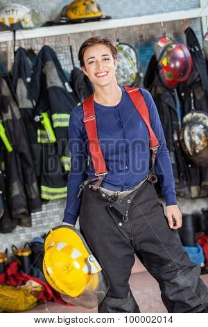 Portrait of confident firewoman holding helmet at fire station