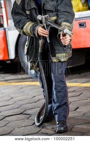 Low section of firefighter holding water hose while standing at fire station