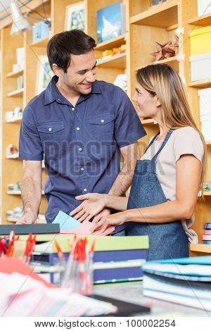 Happy mid adult man looking at saleswoman in store