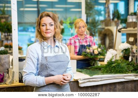 Portrait of confident female florist with colleague working in background at shop