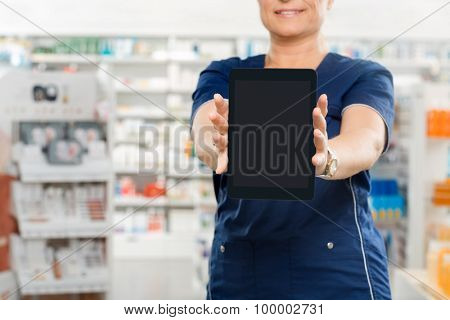 Midsection of mature female pharmacist showing digital tablet with blank screen in pharmacy poster