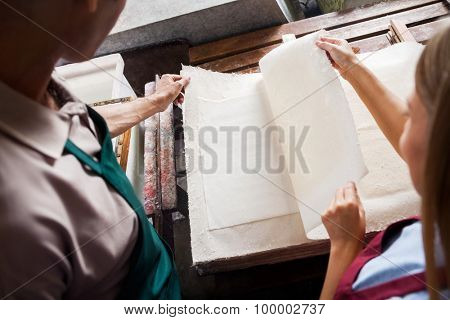 Male and female colleagues checking papers together in factory