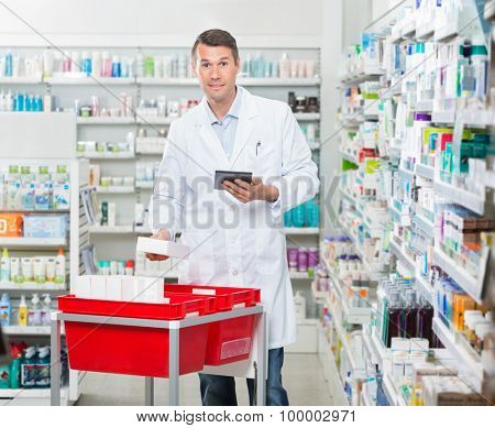 Portrait of mid adult male pharmacist counting stock while holding digital tablet at drugstore