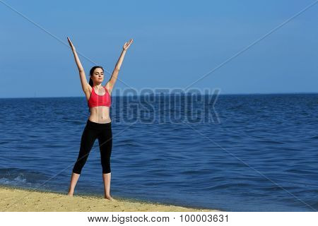 Young sporty woman doing exercise on beach