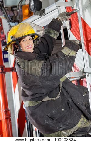 Side view portrait of happy firewoman standing on truck at fire station