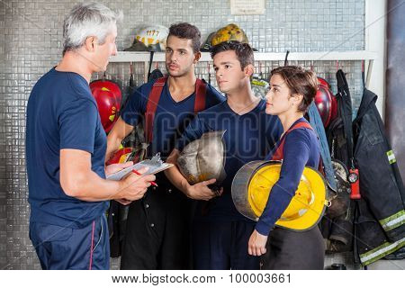 Mature fireman discussing plan with team at fire station
