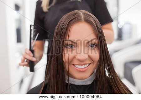 Cheerful young hairdresser is cutting hair of her client