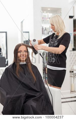 Beautiful young hairstylist is serving her client