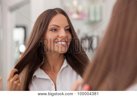 Attractive young woman is satisfied with her hairstyle