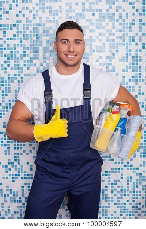 Handsome young male janitor is cleaning the house