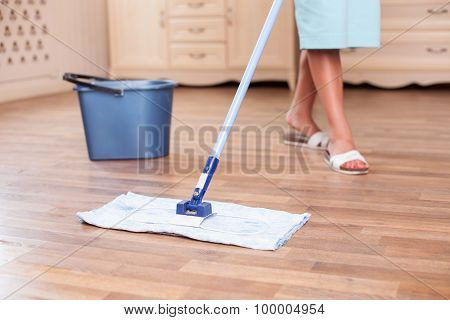 Skilled young housewife is cleaning floor with a mop