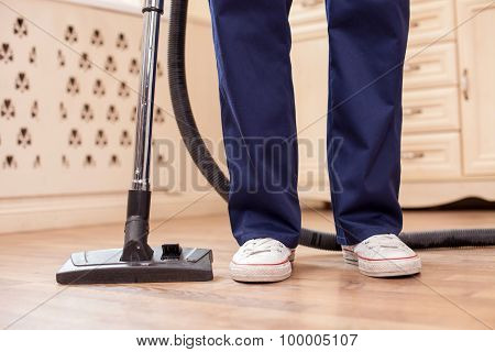 Skilled young man is doing clean-up in a room