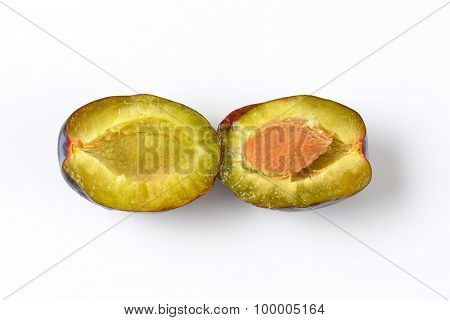 halved ripe plum on white background