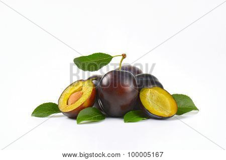 ripe plums with leaves on white background