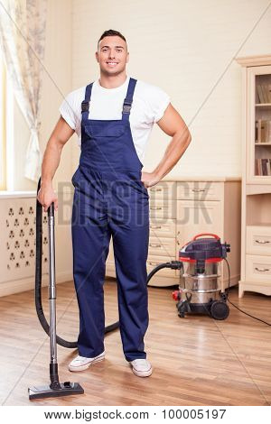 Attractive young man is cleaning flooring in a house