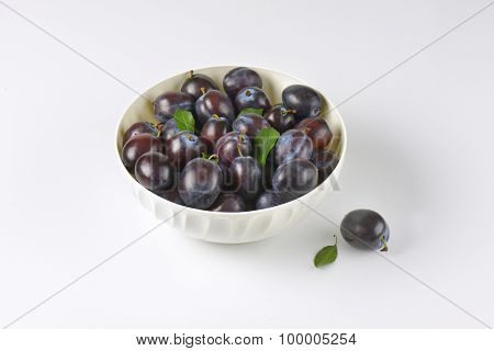 bowl of ripe plums on white background