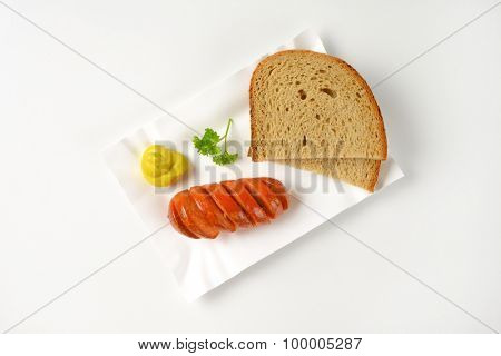 roasted sausage, mustard and bread slices on paper plate