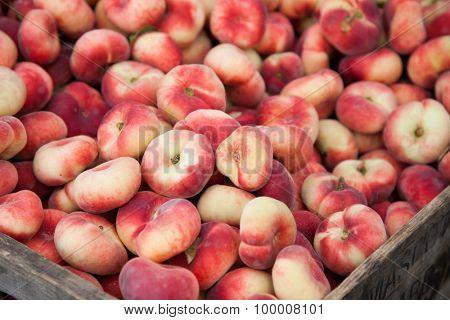 Box of fine ripe flat peaches