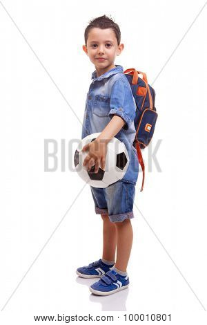 School boy standing with a soccer ball and backpack on white background