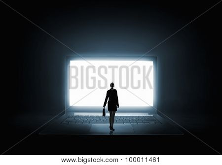 Woman standing on big laptop