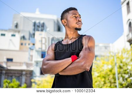 A handsome athlete arm crossed on a sunny day