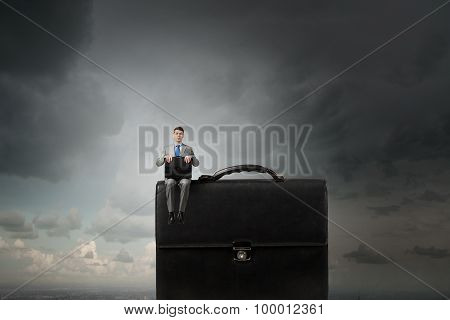 Businessman on big suitcase