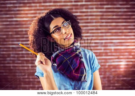 Daydreaming attractive hipster holding pen against red brick background