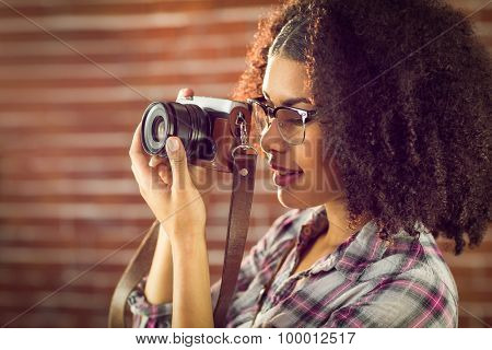 Attractive hipster photographing with camera against red brick background