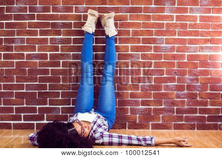 Attractive hipster lying on ground and holding legs up against red brick background