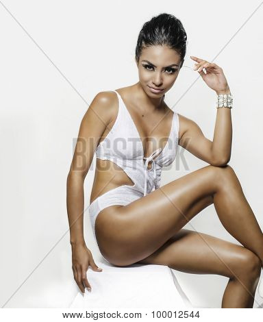 Beautiful exotic young woman wearing white swimsuit