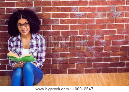 Portrait of attractive hipster sitting and reading book against red brick background