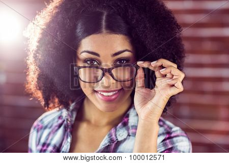 Portrait of attractive hipster posing with glasses against red brick background