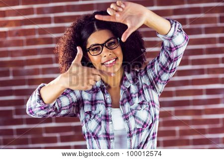 Portrait of attractive hipster taking picture with hands against red brick background