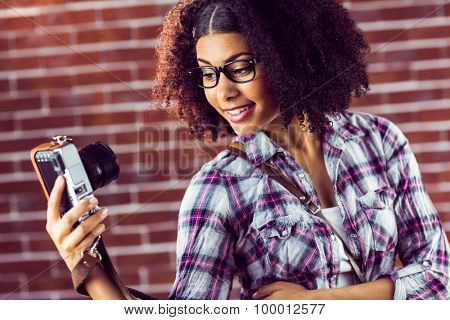 Attractive hipster taking selfies with camera against red brick background