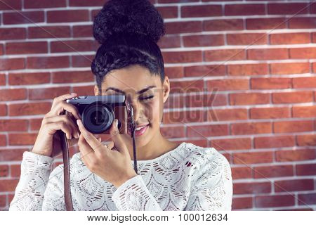 Young hipster taking a picture against a brick wall