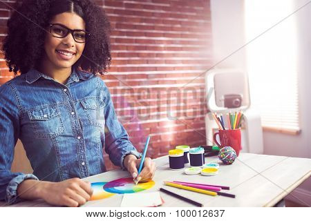 Portrait of casual female designer smiling and drawing at workplace