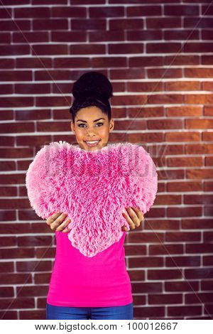 Portrait black hair model holding a pink heart shaped pillow on a red brick wall