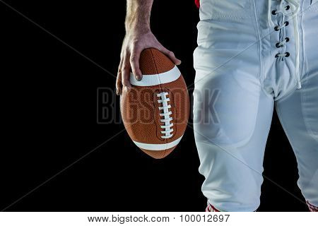 American football player holding football against black background