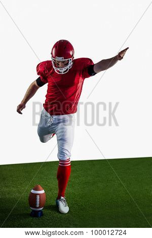 American football player kicking football on american football field