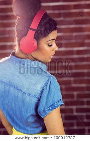 Pretty young woman with headphones leaning against a red brick wall