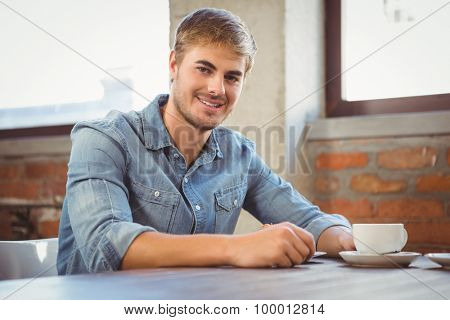 Portrait of handsome man having cup of coffee at coffee shop