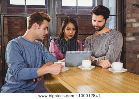 Group of friends enjoying a coffee with a tablet in a cafe