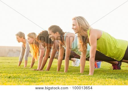 Sporty women doing push ups during fitness class in parkland