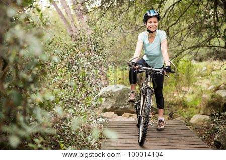 Smiling fit woman taking a break on her bike on a wooden path