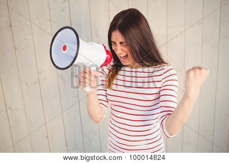 Pretty hipster shouting through megaphone on wooden planks background