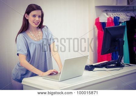 Shop worker using laptop by the till in fashion boutique