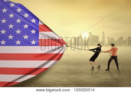 Two Businesspeople Pulling An American Flag