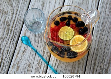 Glass pitcher with fresh juice and seasonal fruit