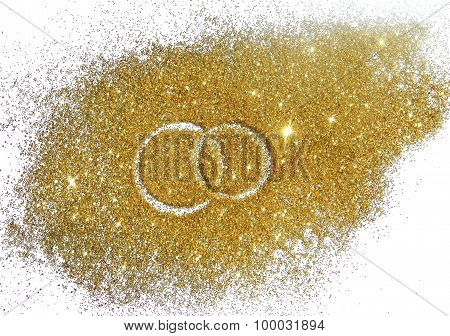 Two wedding rings on gold glitter sparkle on white background