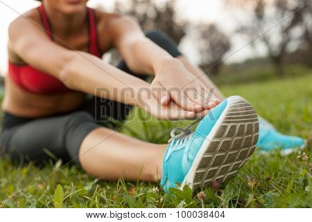 Pretty young woman is exercising in park